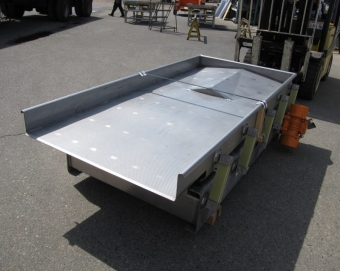 In-line spreader for plate freezer or blancher